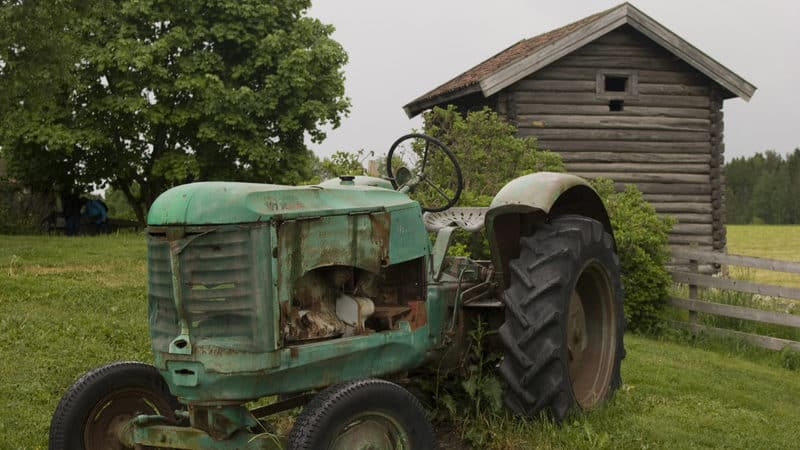 Old tractor in front of barn on a field for essay on childhood memories stir the heart Image