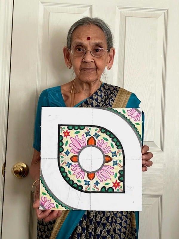 Older Indian woman in traditional sari with kolam