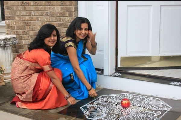 Two young Indian women in traditional saris on front porch with kolam