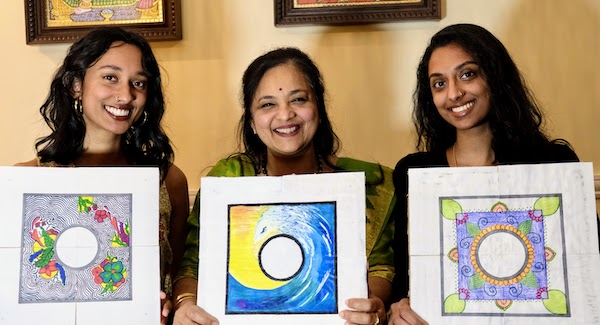 Three Indian women with kolams