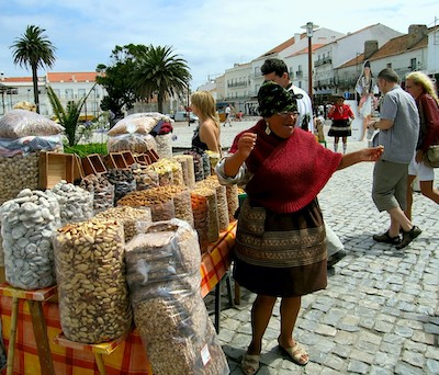 PHOTO: Portuguese tradeswoman selling dried fruits and nuts in the national dress, highlighting Nazare traditions and historic culture