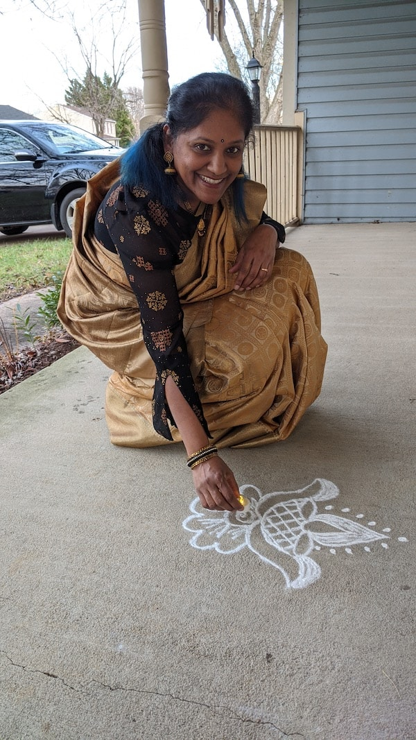 Indian woman drawing kolam in front of house