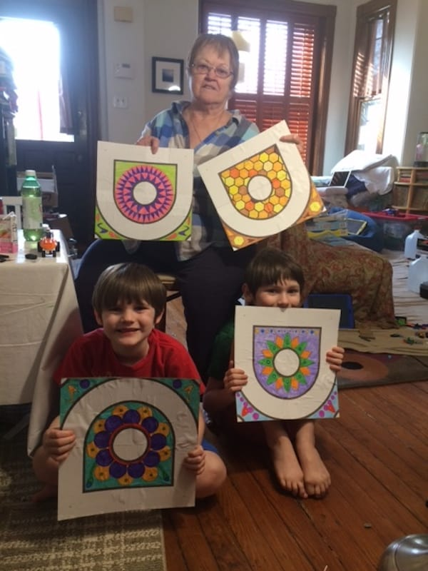 Grandmother and grandkids with several hand crafted kolams