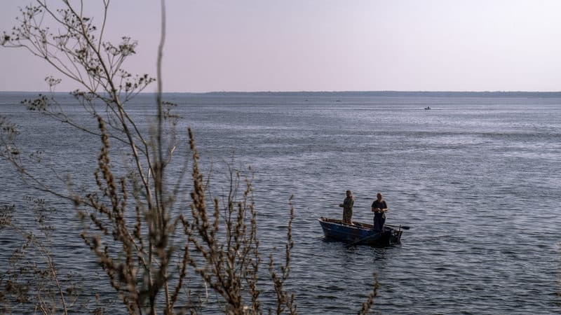 Two men fishing on a lake for article on Ditching worries and finding closure Image