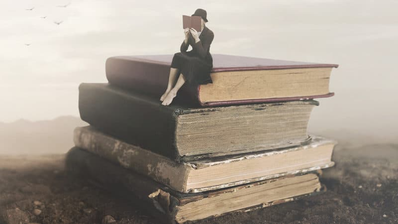 Surreal picture of a woman reading on top of a stack of old books. For Book recommendations for summertime reading Image