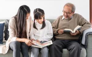 Multigenerational family - Asian mom, daughter, and granddad reading on family sofa, for