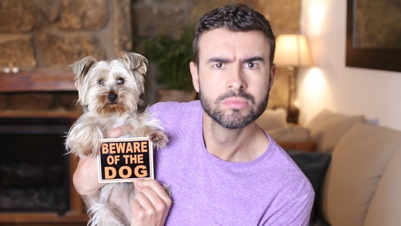 Man holding small dog and Beware of the Dog sign. For article on
