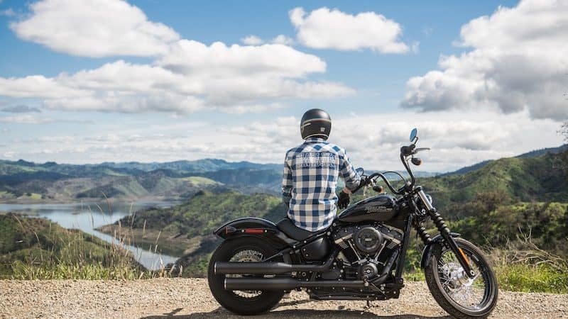 Motorcyclist sitting on motorcycle looking over lake and valley. For 5 Motorcycle Road Trip Tips Image