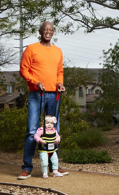 Jeffrey Nash demonstrates his invention, Juppy, as adults assist children who are learning to walk. Nash demonstrated the courage to start again with a fresh, new career