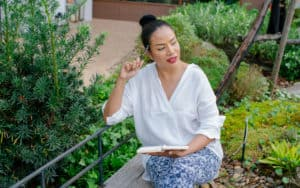 woman contemplating and journaling in a peaceful garden setting - for