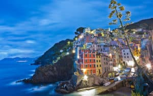 Riomaggiore, one of the Cinque Terre towns, is aglow at night. Credit, Rick Steves' Europefor Sciacchetrà wine and traditions Image