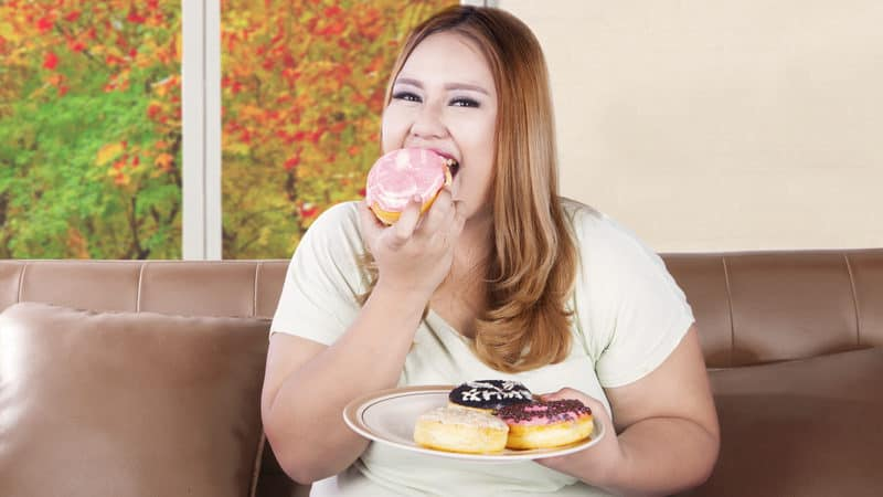 Obese daughter eating donuts Image