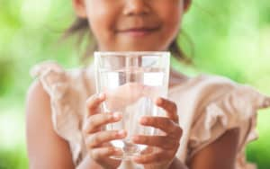 Little girl with a glass of water practicing hydration Image