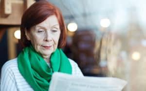 Senior woman reading political negativity Image
