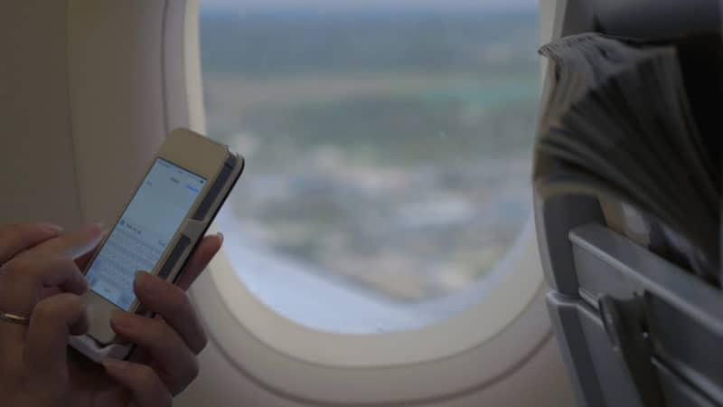 Woman texting on airplane flight Image