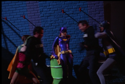 In Enter Batgirl, Exit Penquin, Batman and Robin have to pull apart the thugs who have ganged up on the heroine.