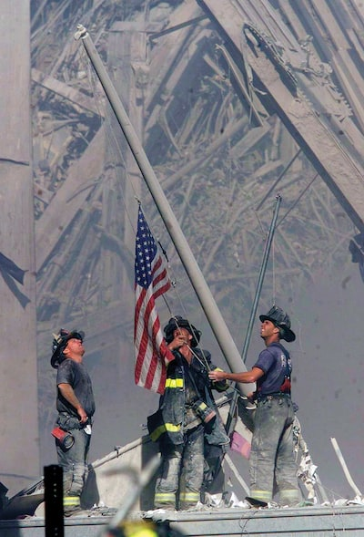 Sept. 11, 2001: Firefighters raise a U.S. flag at the site of the World Trade Center after two hijacked commercial airliners were flown into the buildings Sept. 11, 2001 in New York.