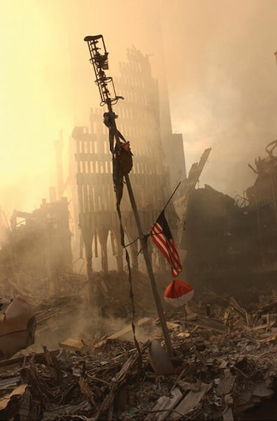 394479 11: A US flag flies from a television antenna September 13, 2001 amid the rubble of the World Trade Center after an aircraft crashed into it September 11 as part of a terrorist attack. The antenna was once at the top of one of the 110 story twin towers. (Photo by FEMA/Getty Images)