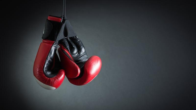 Red boxing gloves hanging over a black background. Credit Refat Mamutov, Dreamstime. For article, Can Boxing Classes Help with Parkinson's? Image