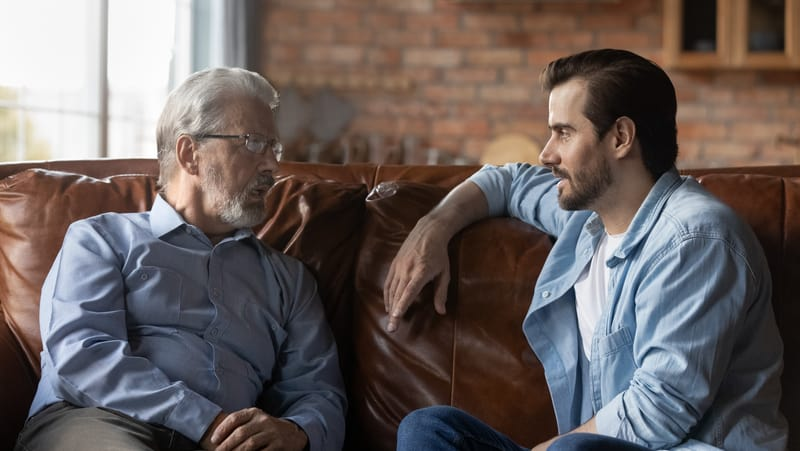 father and son talking at home. Photo credit, Fizkes Dreamstime. For article on A Parkinson's Disease Caregiver Story Image