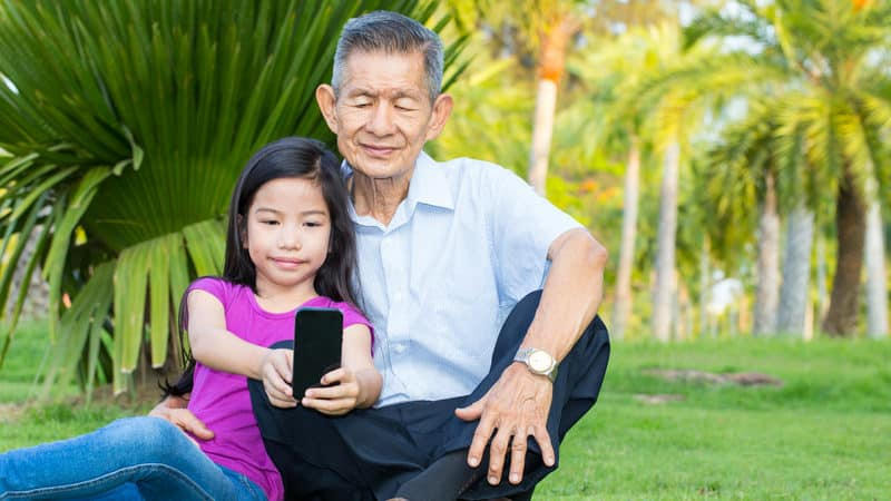 Reflections on Aging and Life - grandfather and granddaughter in parking looking at smartphone Image