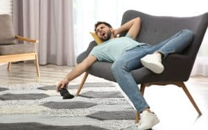 lazy young man lying on a love seat holding a video game controller. For article on A Baby Boomer's Take on a Zoomer's Future Image