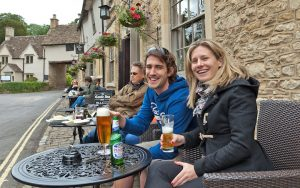 Customers enjoying a beer outside a pub in the Cotswolds, England. Walking Through England's Quaint Cotswolds Image