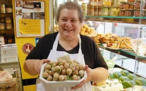 Woman in a French shop holding a platter of escargot. Credit: Rick Steves Europe. For article on the French Passion for Fine Points in Cuisine Image