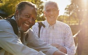 Two older men smiling, standing by a fence. For article on Should friend have reached out? Image