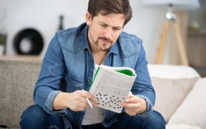 Man doing puzzle, sitting on a sofa Image